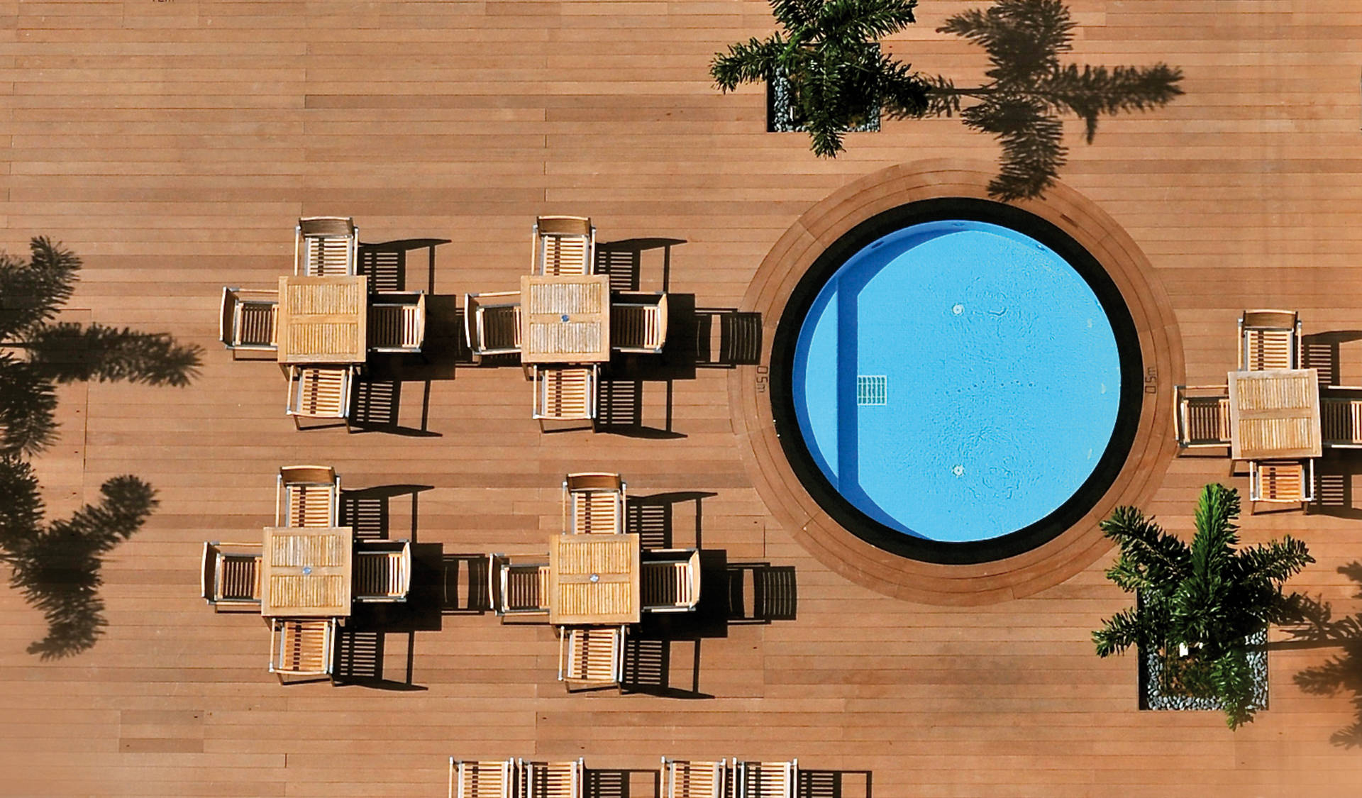 Slip-resistant terraces from verando from resysta at an outdoor pool.